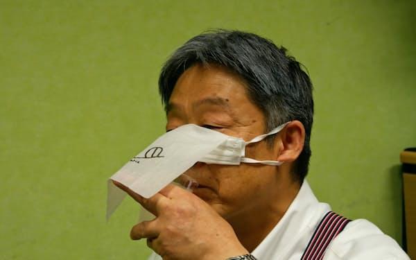 装着したまま食事できるマスクの利用法を実演する堀埜一成社長