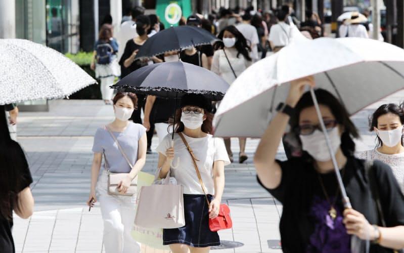 強い日差しの下、日傘を差して歩く人たち(名古屋市中区)