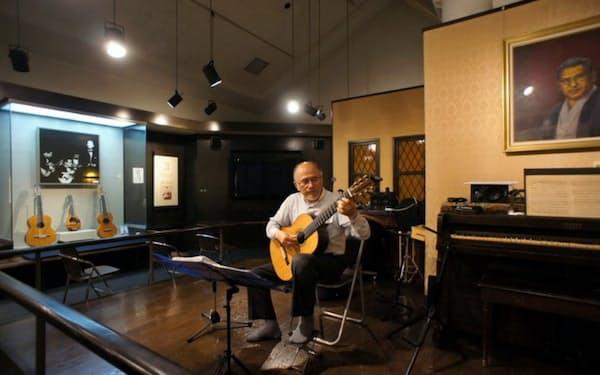 復元したレッスン室をステージに演奏する山田館長。古賀氏の気持ちを音で伝える(福岡県大川市)