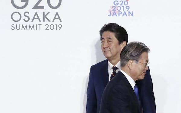6月、G20大阪サミットで握手した後、すれ違う韓国の文在寅大統領(手前)と安倍首相=大阪市(聯合=共同)