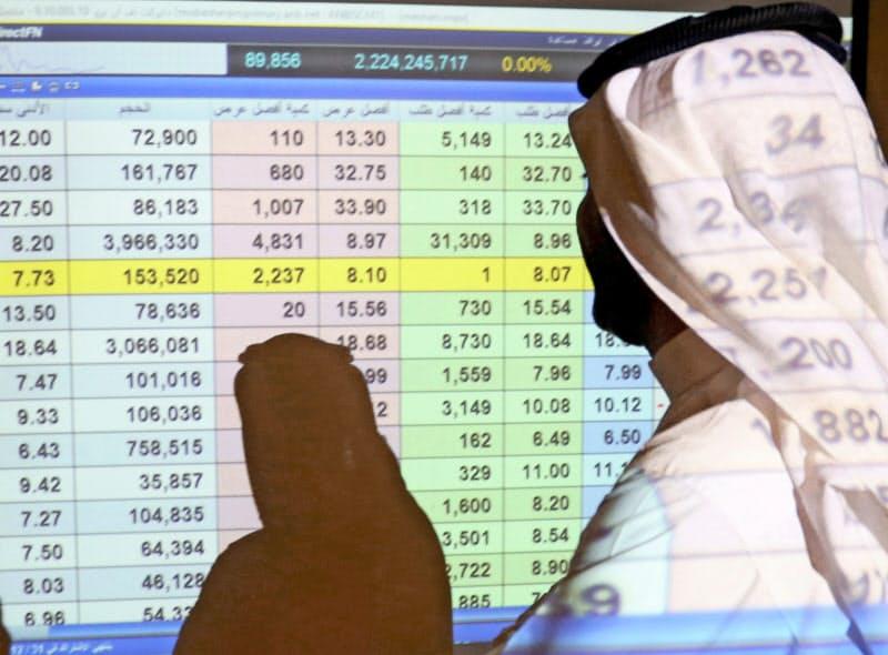 リヤドの銀行前でスクリーンに表示された株価をながめるサウジ人=ロイター