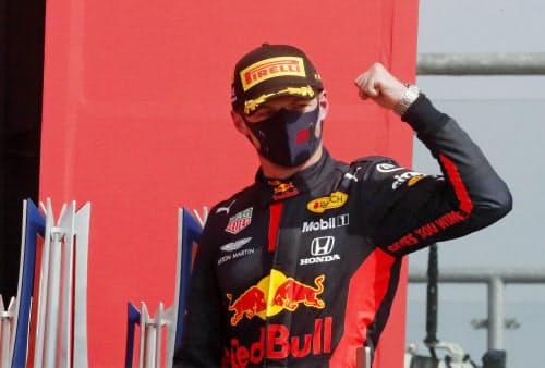F1の70周年記念GPで優勝し、表彰台でガッツポーズするレッドブル・ホンダのマックス・フェルスタッペン(9日、シルバーストーン)=ロイター
