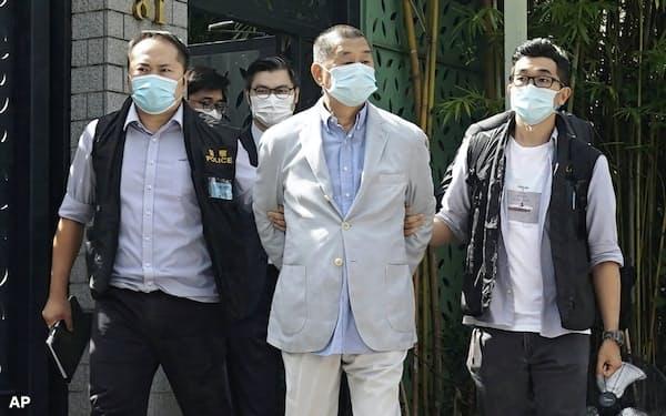 10日、警察に連行される香港紙創業者の黎智英氏(中)=AP
