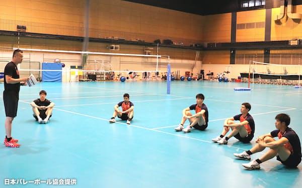 NTCでの合宿再開直後、距離を取って監督の話を聞く選手たち=日本バレーボール協会提供