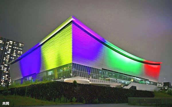 東京五輪の開幕まで1年となり「五輪カラー」にライトアップされた有明アリーナ(東京都江東区)=共同