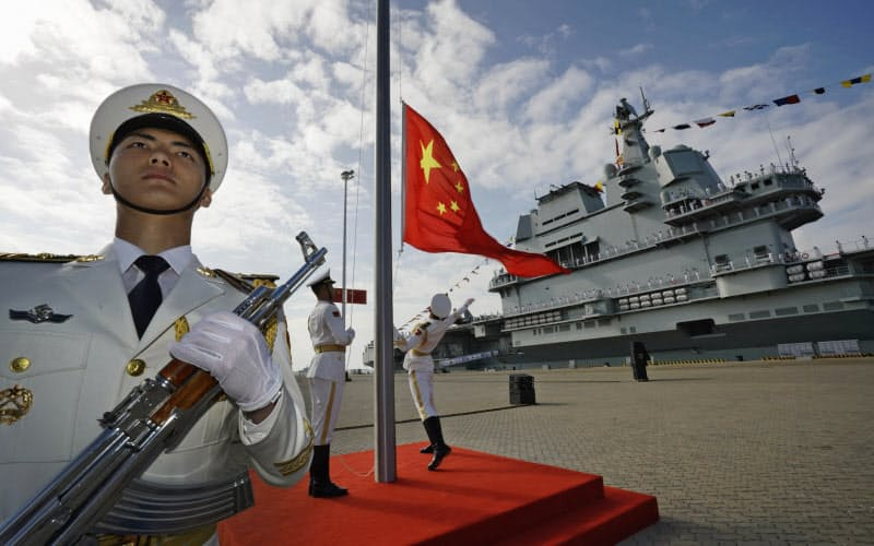 中国の軍近代化は米軍の忠実な後追い(2隻めの空母「山東」の前で国旗を揚げる中国海軍=AP)