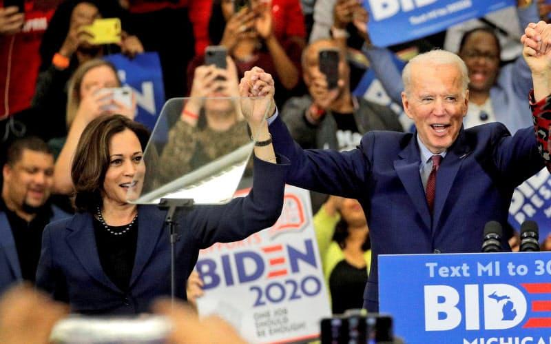 バイデン前副大統領(右)と手を取り合うハリス氏(3月、ミシガン州デトロイト)=ロイター
