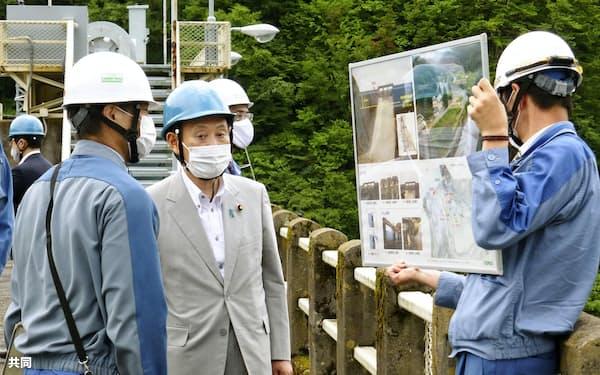 須田貝ダムを視察し、関係者から説明を聞く菅官房長官(中)(12日、群馬県みなかみ町)