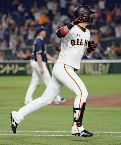 9回巨人2死一、三塁、中前にサヨナラ打を放ち、一塁に向かう代打亀井。奥は投手マクガフ(13日、東京ドーム)=共同