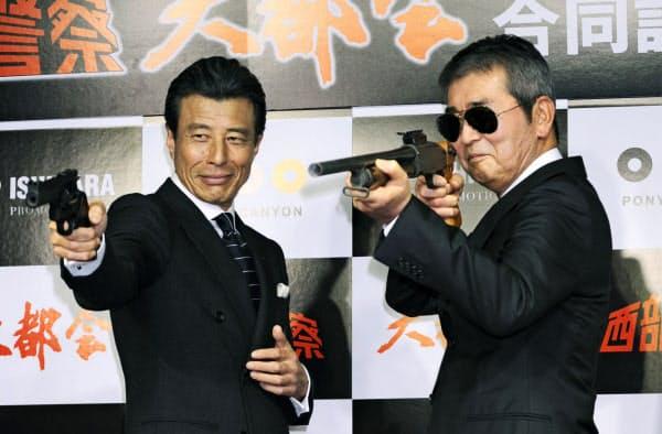 2012年1月、サングラス姿で銃を構える渡哲也さん。左は舘ひろしさん(東京都内)=共同