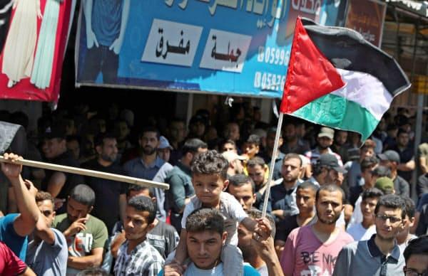 14日、パレスチナ自治区ガザで反UAEデモに参加する人々=ロイター