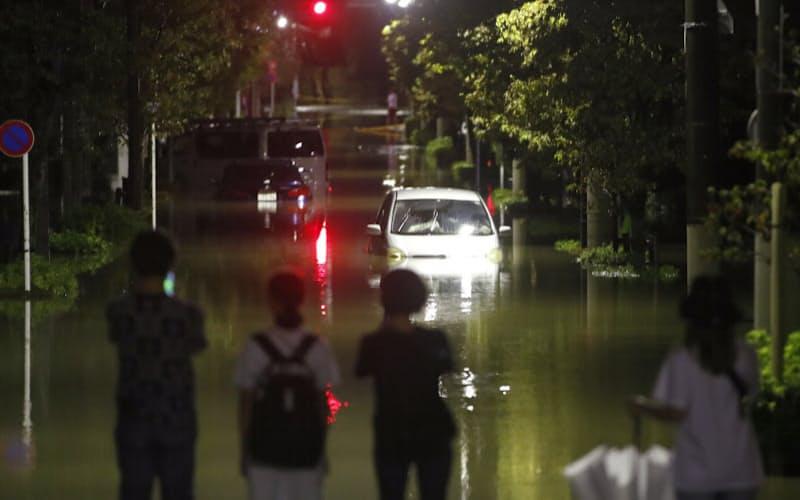 台風19号による大雨で冠水した住宅地の道路を見つめる人たち(2019年10月12日、東京都世田谷区)=共同