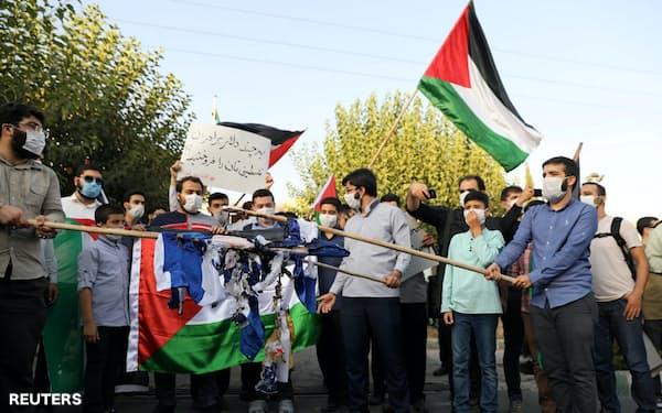 UAE大使館の前でイスラエル国旗を燃やして国交正常化に抗議するイランの人々(15日、テヘラン)=WANA・ロイター