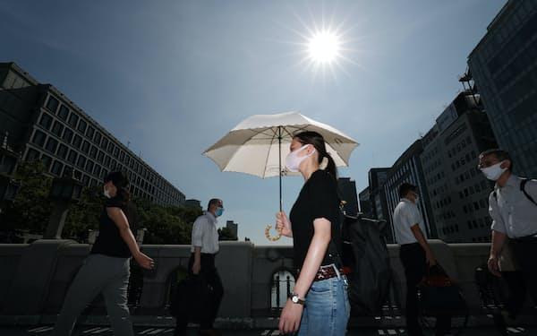 強い日差しの下、日傘をさして歩く人たち(19日午前、大阪市北区)