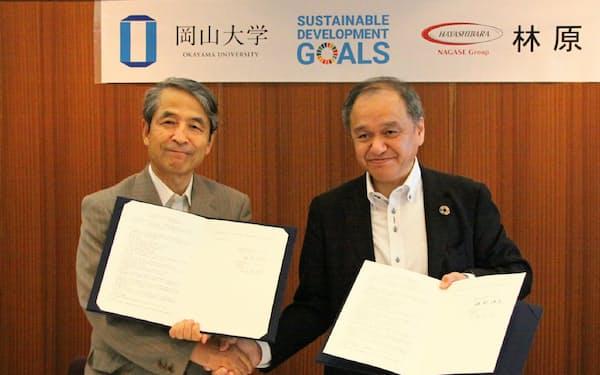 協定書を手に握手する林原の安場社長(右)と岡山大の槙野学長(19日、岡山市)