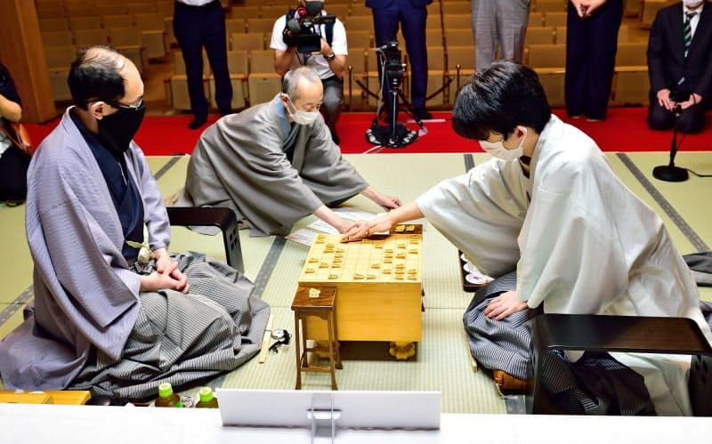 王位戦第4局の2日目に封じ手を指す藤井棋聖。左は木村王位(20日午前、福岡市)=日本将棋連盟提供