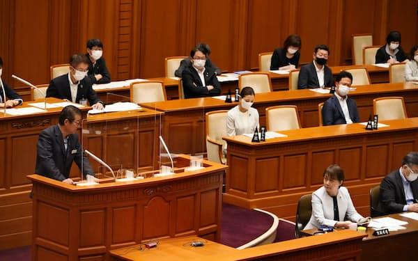 大阪市議会の本会議場で議論する松井市長(左)と自民党の北野議員(手前右)(21日、大阪市役所)