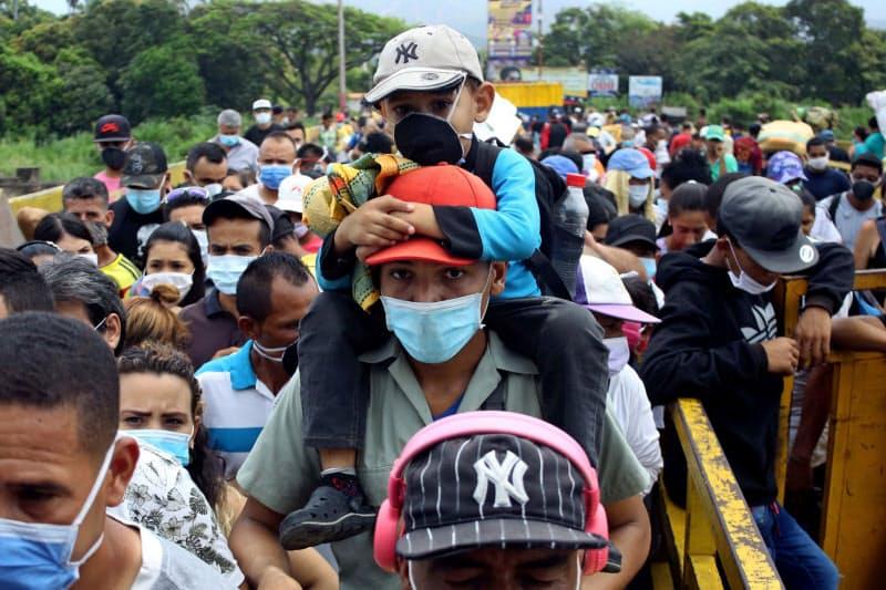 コロンビアとベネズエラの国境にかかる橋を渡る人々(3月、コロンビア北部ククタ)=ロイター