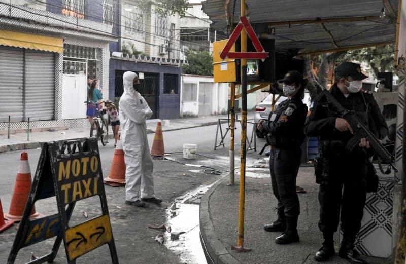 新型コロナの被害が深刻な地域を巡回する警官(5月、リオデジャネイロ)=ロイター