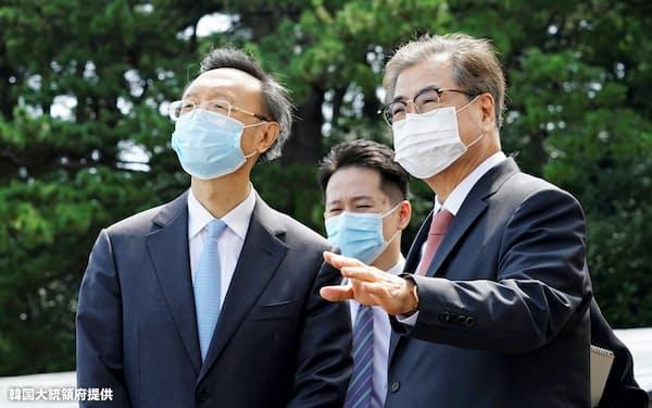 訪韓した中国の楊潔篪共産党政治局員(左)と韓国の徐薫国家安保室長(22日、釜山)=韓国大統領府提供
