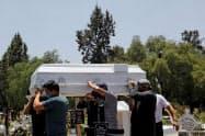 新型コロナで亡くなった家族の棺おけを運ぶ人々(22日、メキシコシティ)=ロイター