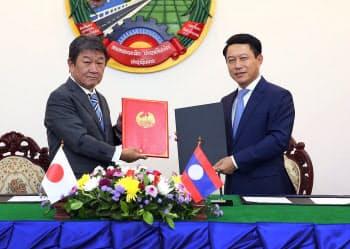 23日、無償資金協力の書簡を交わす茂木外相(左)とラオスのサルムサイ外相=外務省提供