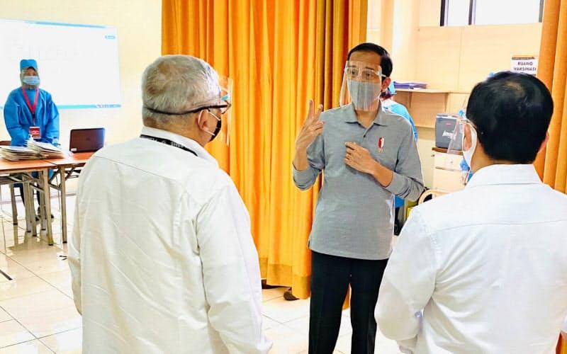 インドネシアのジョコ大統領(中央)は中国から新型コロナウイルスのワクチン供給を受ける国営製薬企業を視察した(11日、バンドン)=大統領府提供・ロイター