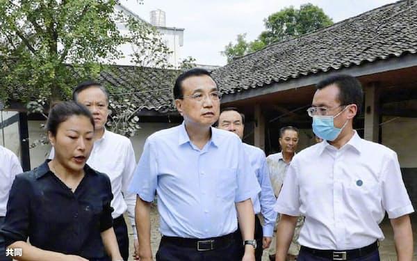 20日、中国重慶市郊外の被災地を視察する李克強首相(中央、中国政府の「微博(ウェイボ)」から)=共同