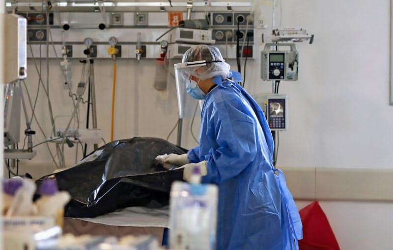 病院で遺体袋を清掃する様子(18日、ブエノスアイレス)=AP