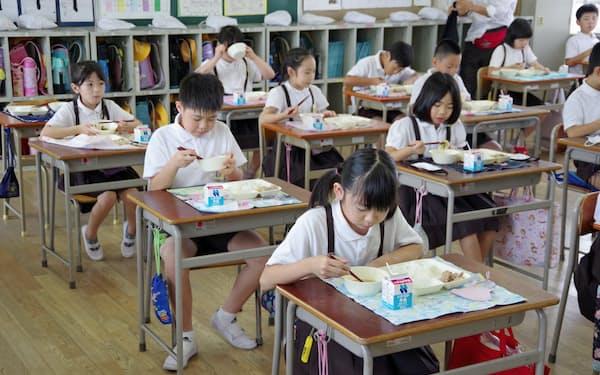 教室で給食を食べる児童ら(25日、大阪市生野区)