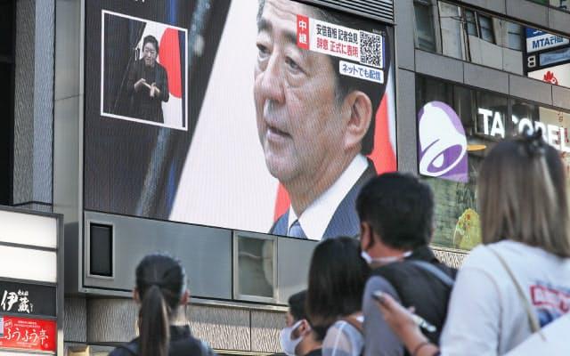 記者会見で辞意を表明した安倍首相を映す街頭モニター(28日、大阪市中央区)