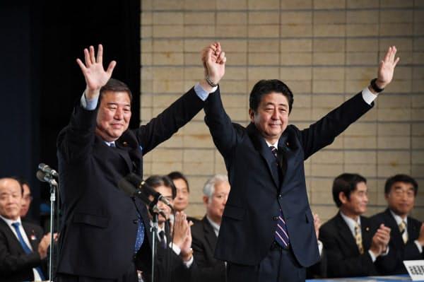 自民党総裁選で石破茂元幹事長(左)を破り、連続3選を果たした安倍首相(2018年9月20日、自民党本部)