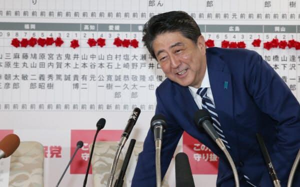 衆院選の開票が進む中、バラが並ぶボードの前で笑顔を見せる安倍首相(2017年10月22日、自民党本部)