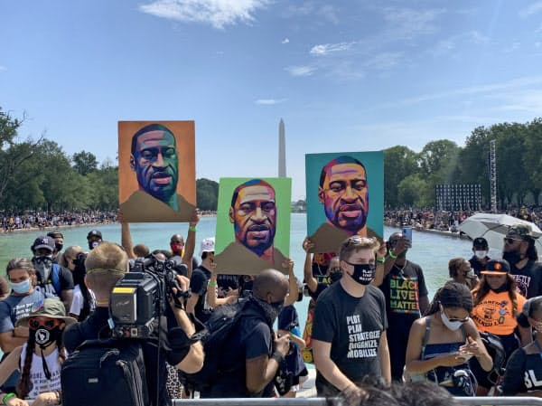 28日、ミネソタ州で白人警官の暴力によって死亡したジョージ・フロイドさんの似顔絵を掲げるデモ参加者(米ワシントン)