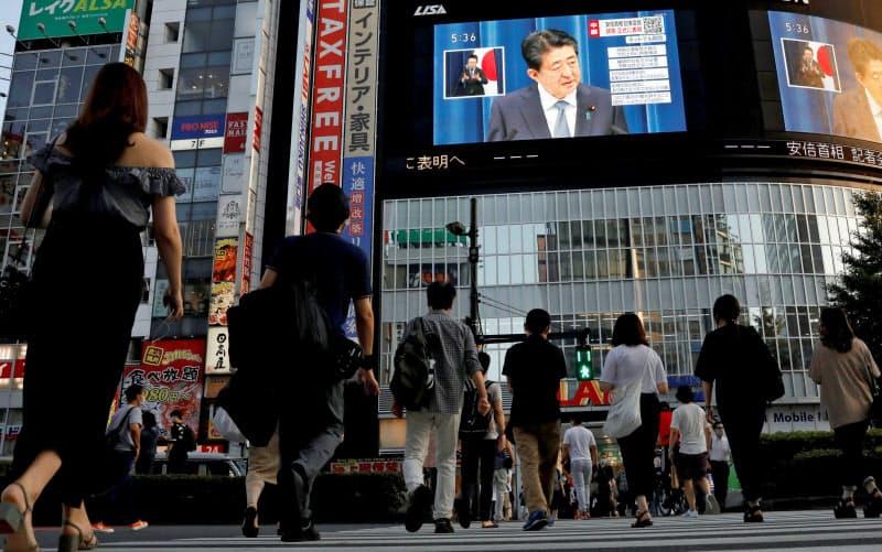 8月28日、安倍首相の辞任会見を映す街頭スクリーンを見る東京の人々=ロイター