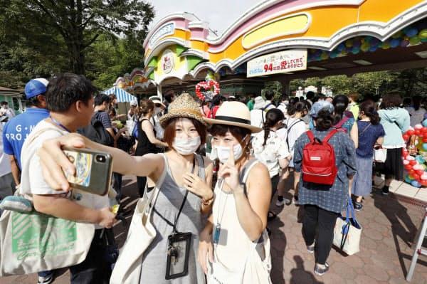 閉園の日を迎えた遊園地「としまえん」を訪れ、記念撮影する女性客ら(31日午前8時59分、東京都練馬区)=共同