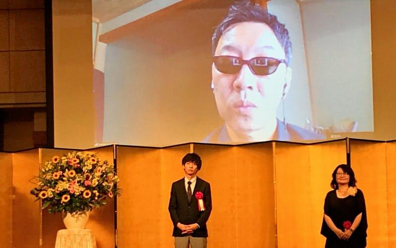 第163回芥川賞・直木賞贈呈式で、写真撮影に臨む芥川賞の高山羽根子、遠野遥。画面はリモートで出席した直木賞の馳星周