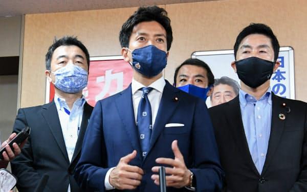 自民党総裁選で党員投票を求める署名を二階幹事長に提出し、記者の質問に答える小林史明青年局長(中)(31日、東京・永田町)