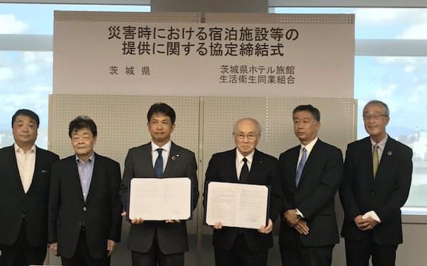 大井川知事(中央左)と吉岡理事長(中央右)が協定に調印した