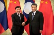 中国の習近平国家主席(右)と握手するラオスのトンルン首相(1月、北京)=ロイター