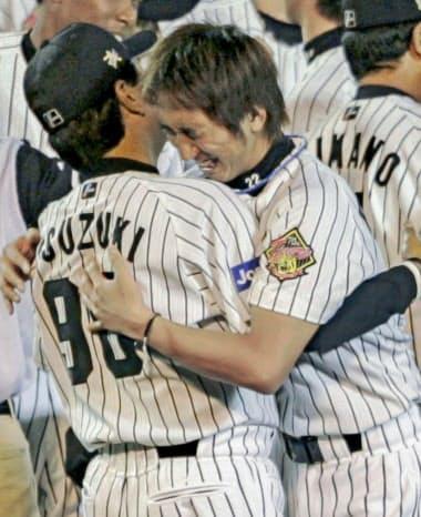 2005年9月、リーグ優勝を決めコーチと抱き合って喜ぶ藤川(右)=共同
