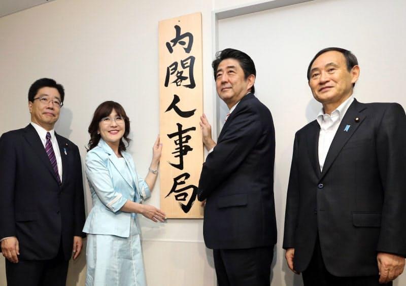 内閣人事局発足で看板かけをする安倍首相(2014年5月、東京・永田町)