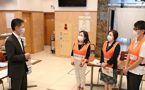 軽症者向けの宿泊療養施設で説明を受ける湯崎英彦知事(4日、広島県内)