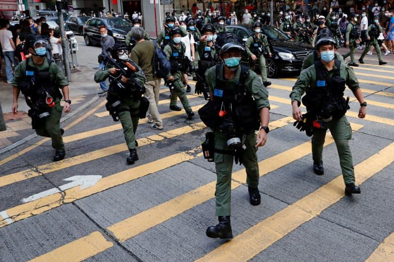 繁華街でデモ参加者を取り締まる警察官(6日、香港)=ロイター