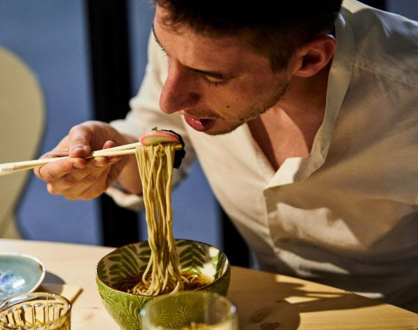 サガミの海外FC1号店でそばを食べる男性(7月、イタリア・モデナ)