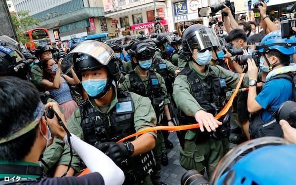 デモを取り締まるマスク姿の警察官ら(6日、香港)=ロイター