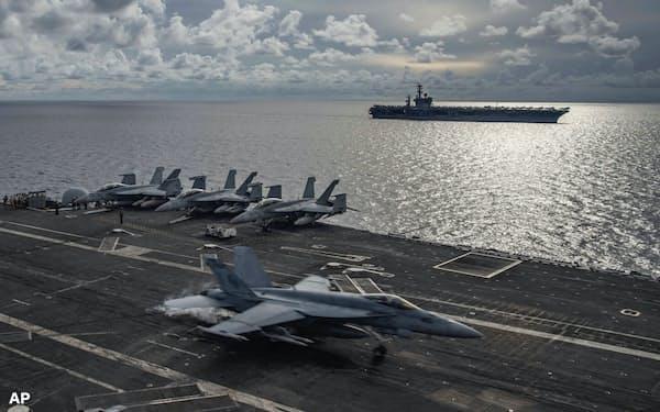南シナ海での演習で米空母ロナルド・レーガン(手前)に着艦するFA18戦闘機と空母ニミッツ(米海軍提供)=AP