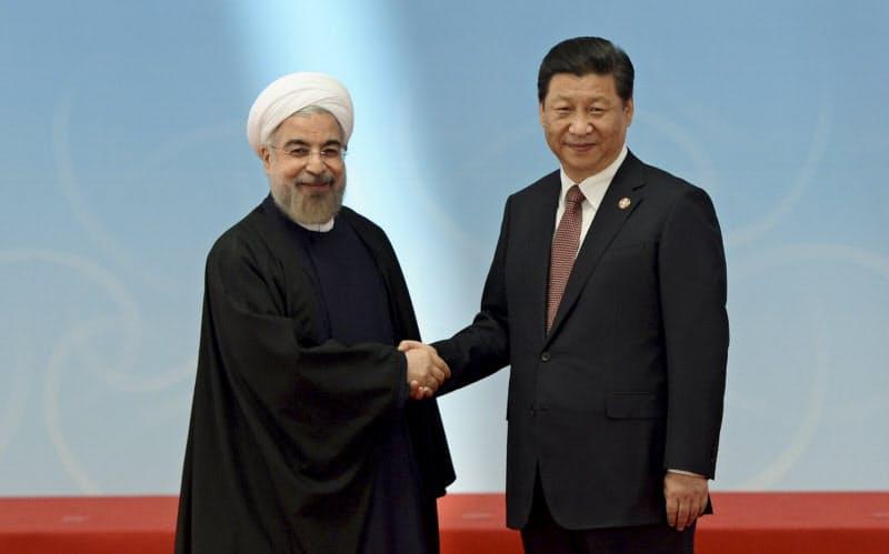 握手するイランのロウハニ大統領(左)と中国の習近平国家主席(2014年上海で)=ロイター