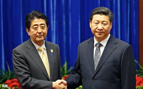 2014年11月、仏頂面をした中国の習近平国家主席(右)と握手する安倍首相(北京の人民大会堂)=共同
