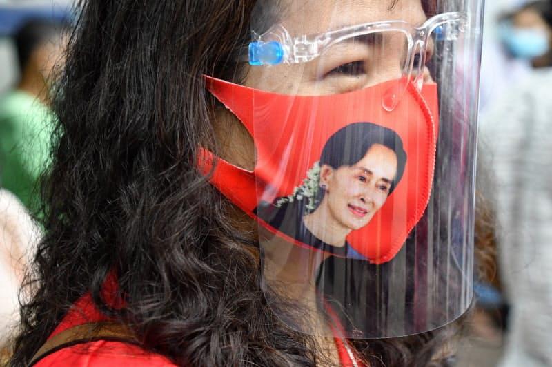 8日、スー・チー氏の写真をあしらったマスク姿で候補者の街頭演説を見守る女性(ヤンゴン)